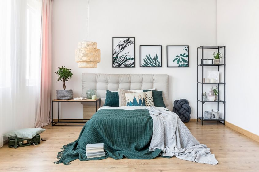 Grey,And,Green,Blanket,On,Bed,Against,White,Wall,With